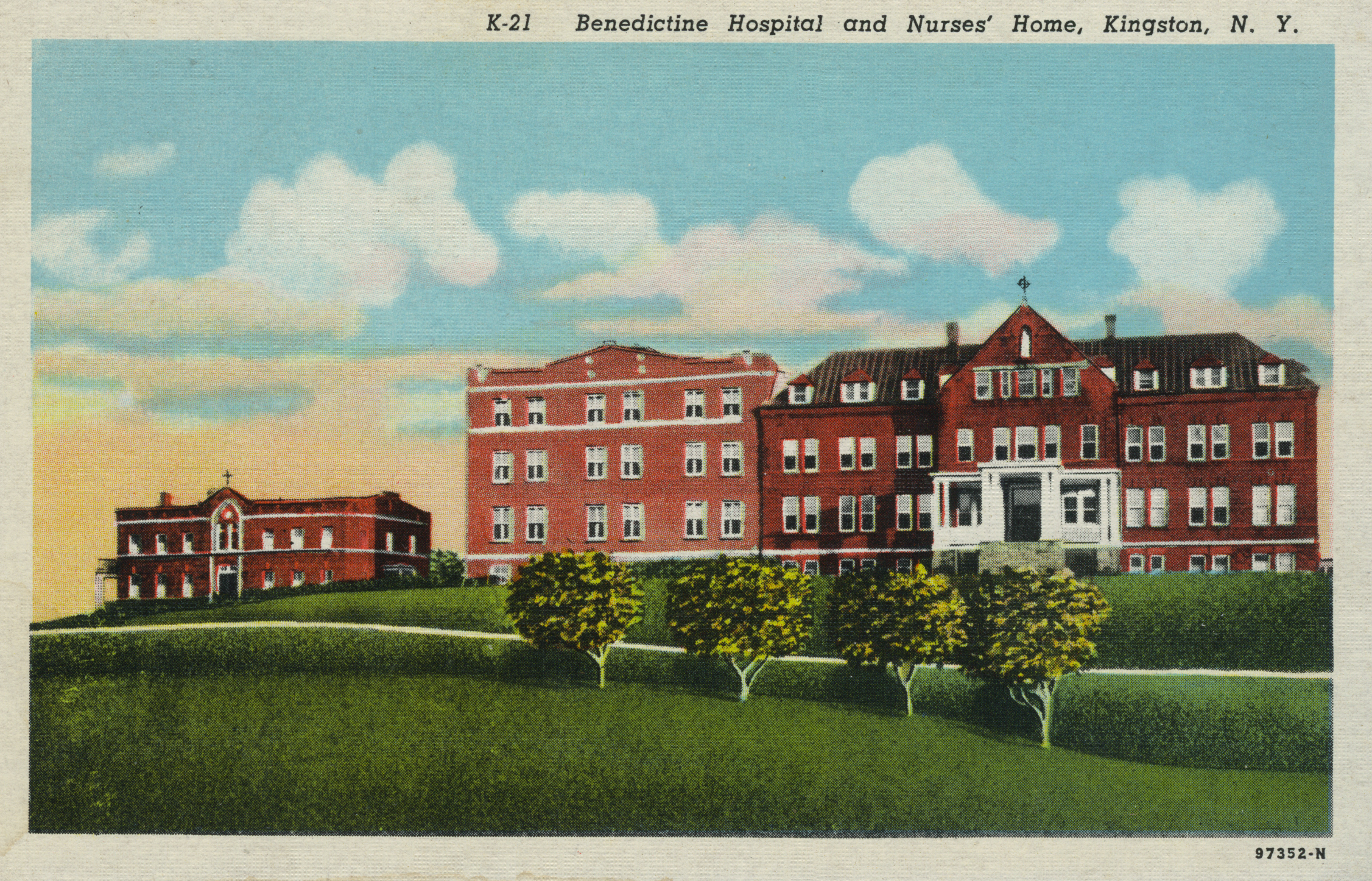red brick three-story hospital building with a red brick two-story nurses' home to the left side. landscaped lawn and trees in front of both buildings.