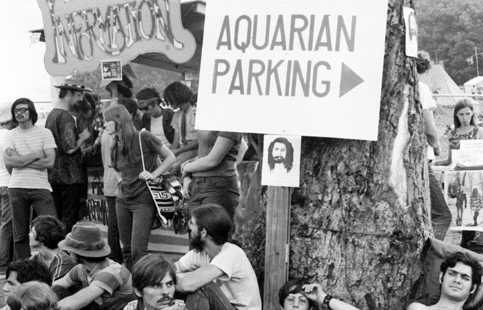 detail of Woodstock Festival photo showing people gathered at an information booth